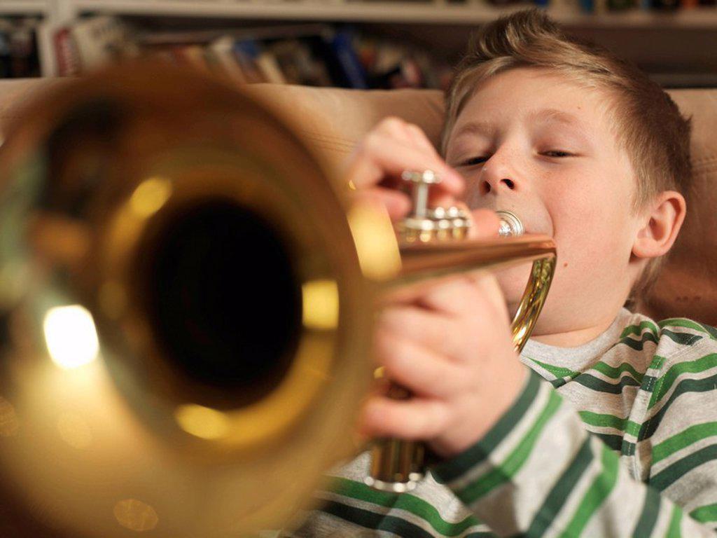 Boy, 11 playing trumpet : Stock Photo