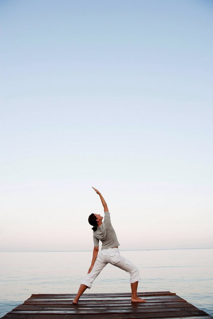 Stock Photo: 1773R-110777 Young Woman Doing Yoga At Jetty