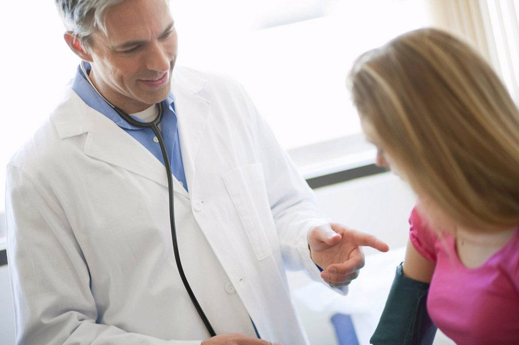Male Doctor examining girl patient : Stock Photo