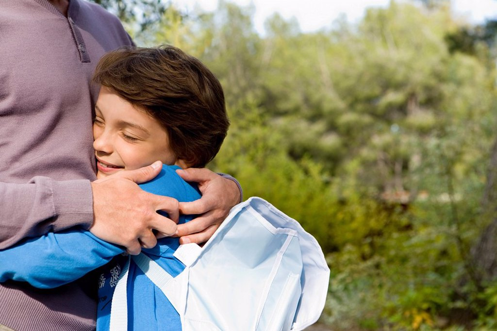 Stock Photo: 1773R-112865 happy boy hugging dad back from school