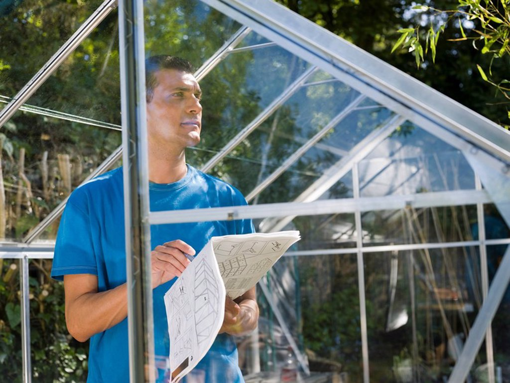 Man building greenhouse in garden : Stock Photo