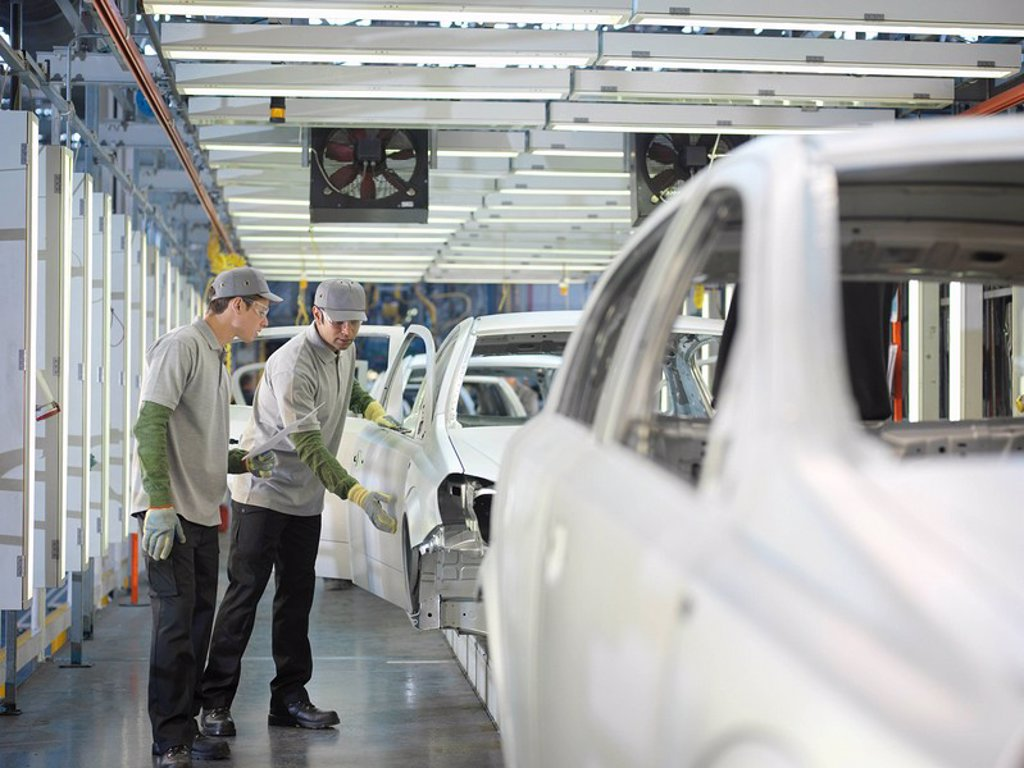 Car Plant Workers Discussing Cars : Stock Photo