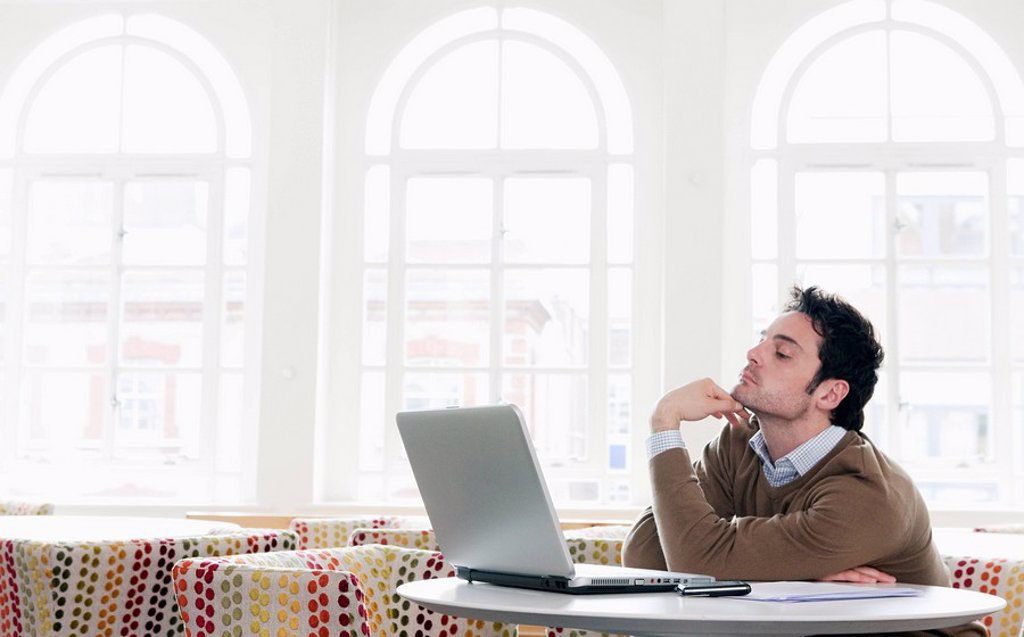 Young man gazing into laptop : Stock Photo