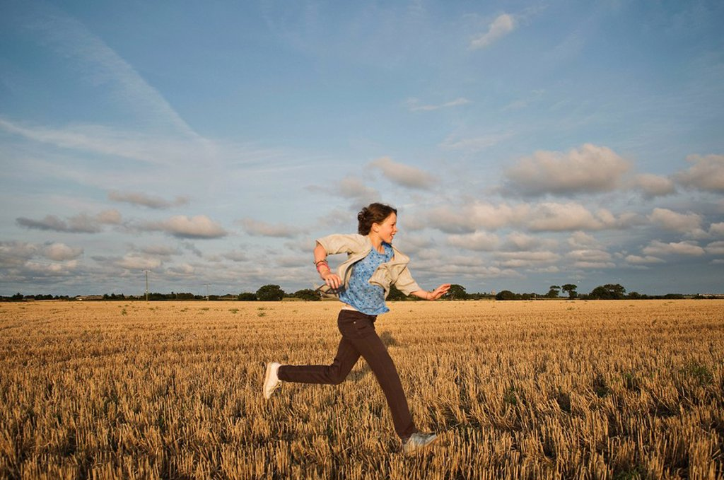 Stock Photo: 1773R-120641 A young girl running through a field
