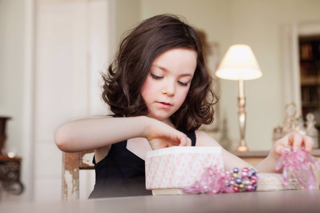 girl exploring contents of parcel : Stock Photo