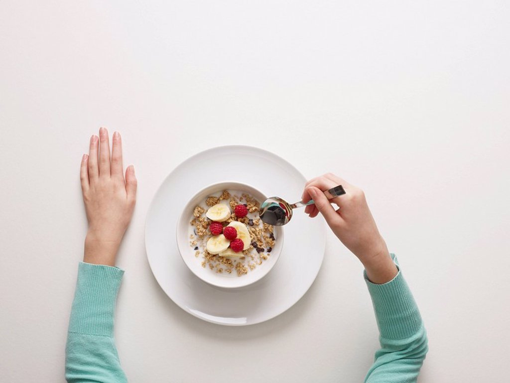 Stock Photo: 1773R-123228 Hands by a bowl of cereal