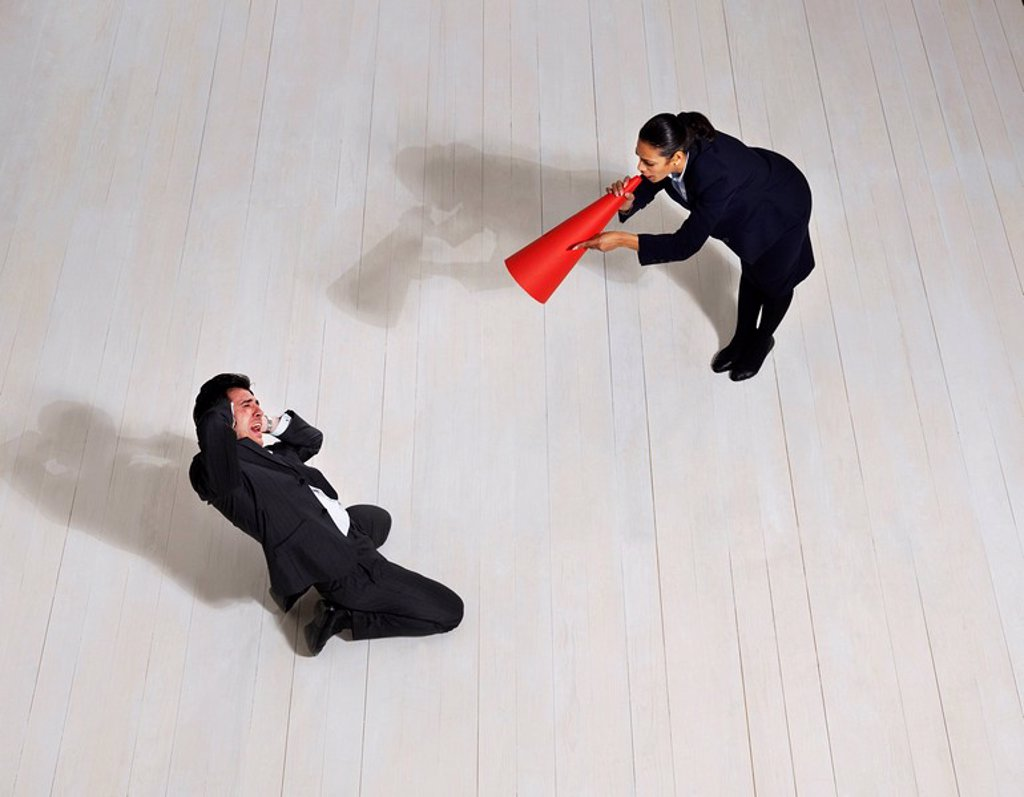 Business woman shouting at man on floor : Stock Photo