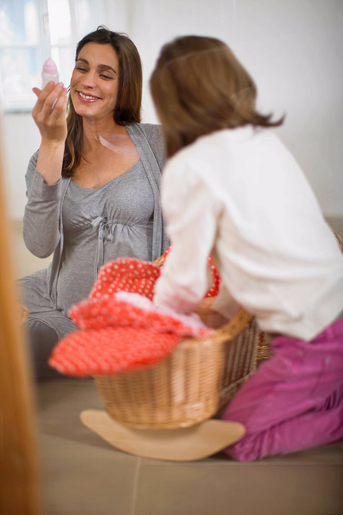 Stock Photo: 1773R-125972 Pregnant woman playing with little girl
