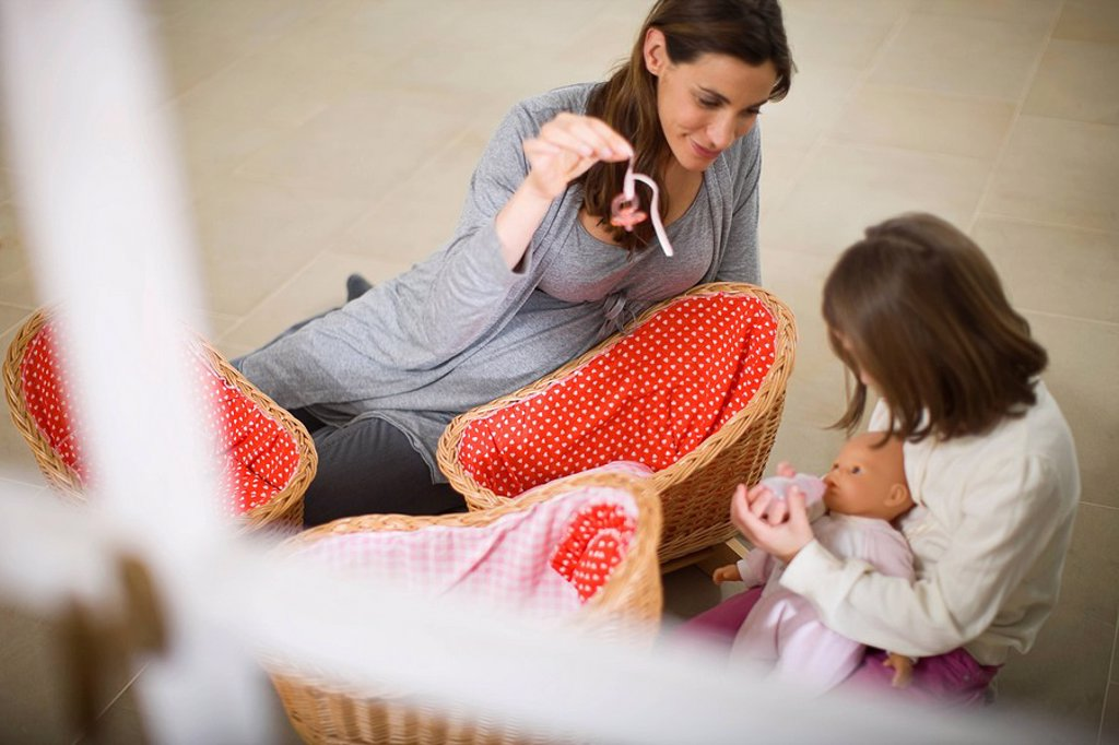 Pregnant woman playing with little girl : Stock Photo
