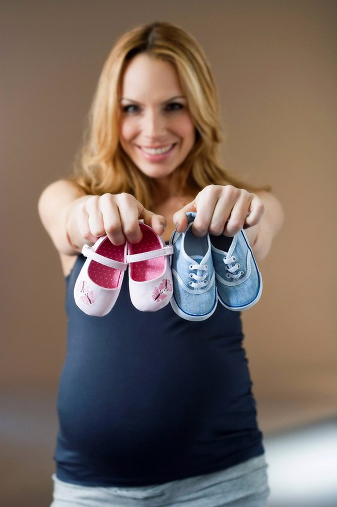 Woman showing baby shoes : Stock Photo