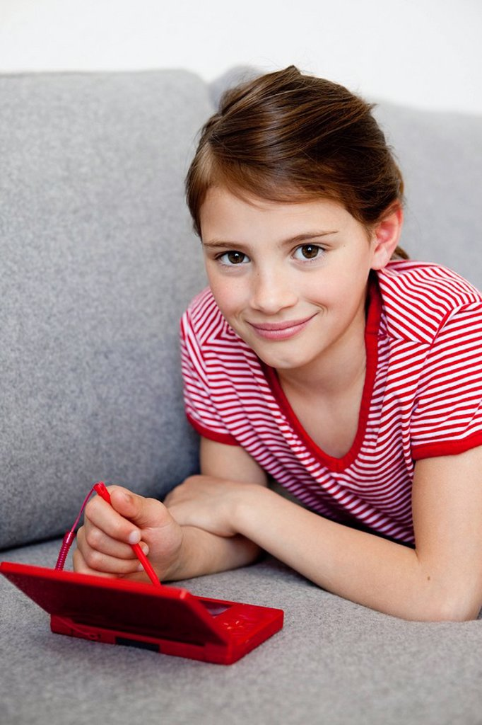 Stock Photo: 1773R-126108 Girl playing video game on couch