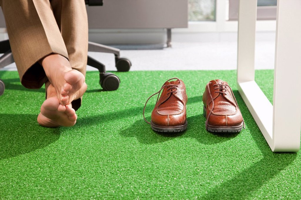 Relaxed feet on a green office carpet : Stock Photo