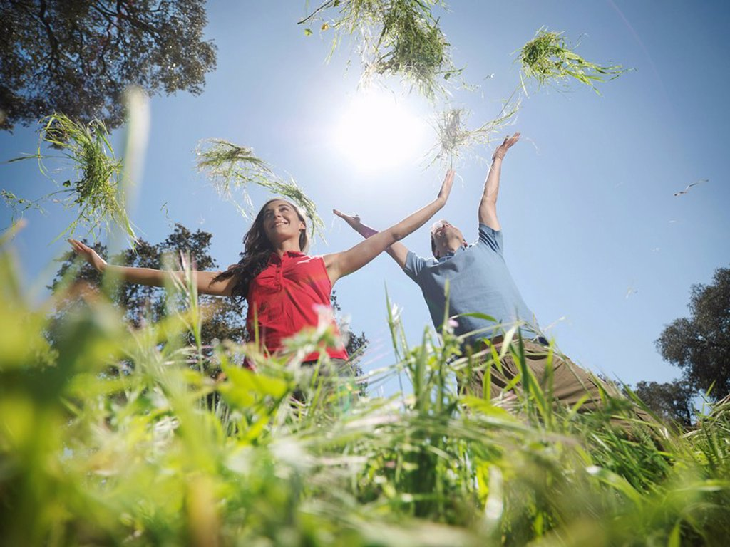 Stock Photo: 1773R-126836 Couple throwing grass in the air
