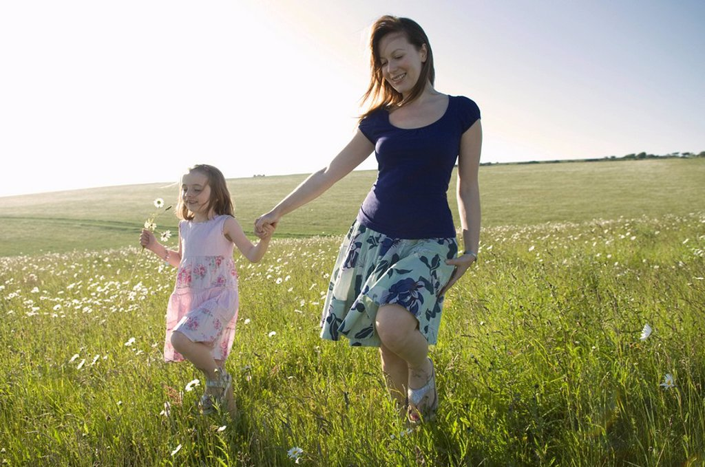 Woman and child walk thru sunny meadow : Stock Photo