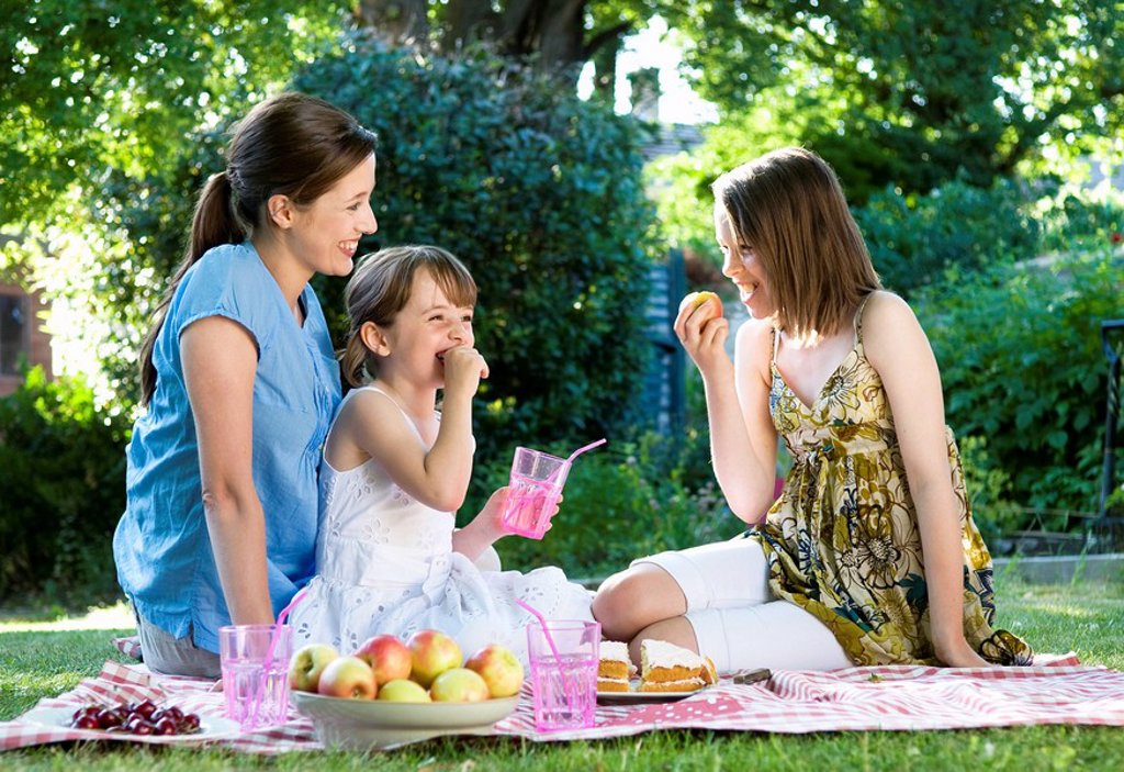 Happy mother and daughters at picnic : Stock Photo