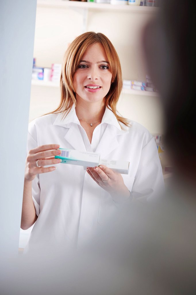Pharmacist looking at pill box : Stock Photo