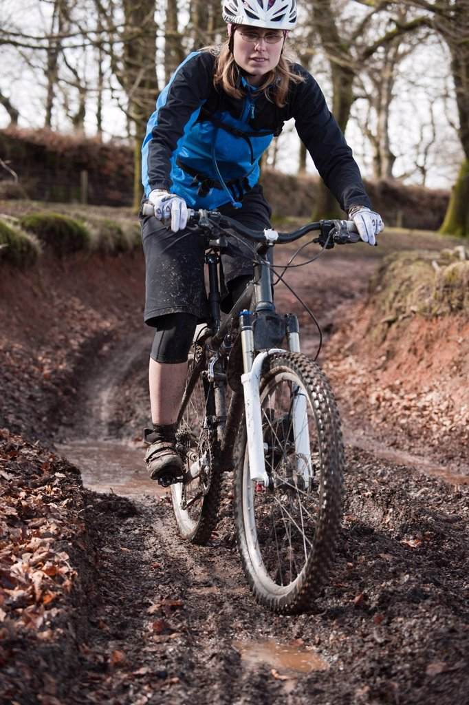 Stock Photo: 1773R-129849 Woman riding mountain bike muddy track