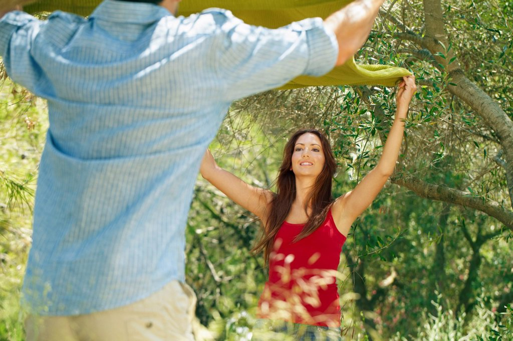 Stock Photo: 1773R-130003 Couple laying out picnic blanket