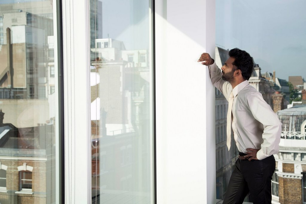 Businessman looking out of office window : Stock Photo
