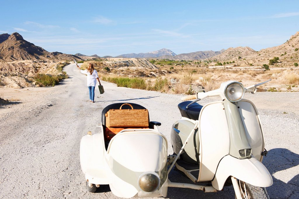 Woman walking away from motorbike : Stock Photo