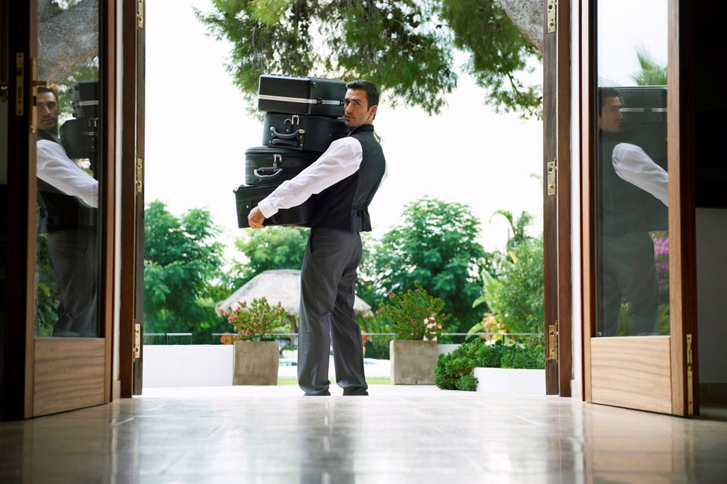 Stock Photo: 1773R-134590 Man carrying suitcases into hotel