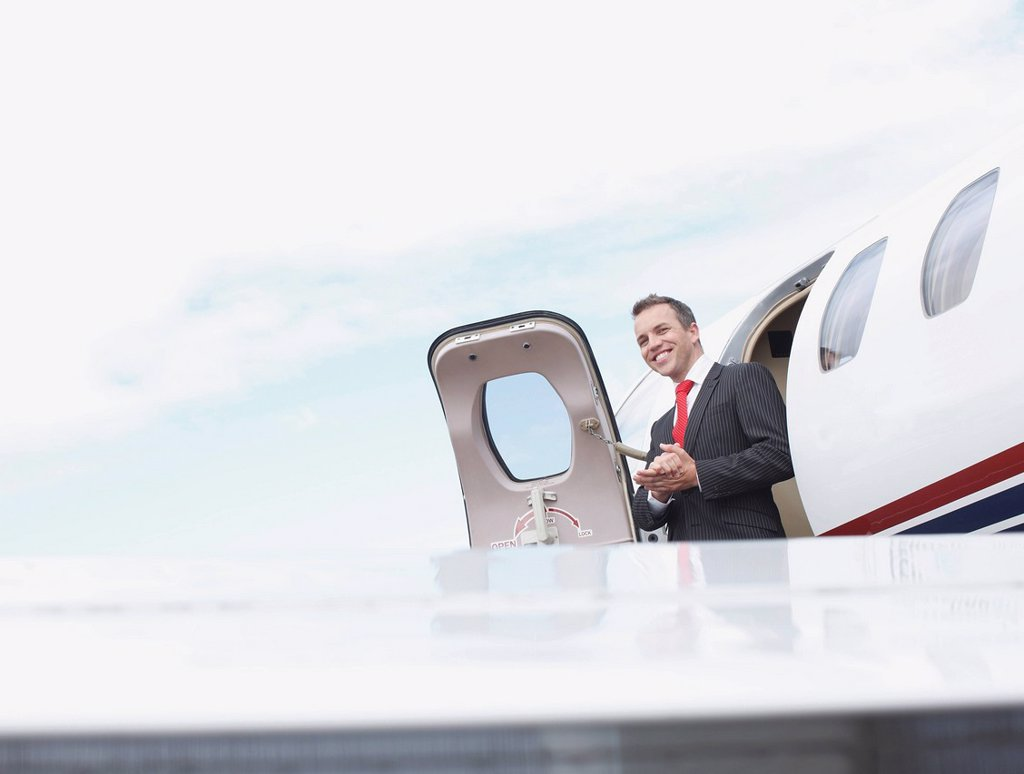 Stock Photo: 1773R-135177 Businessman exiting corporate jet