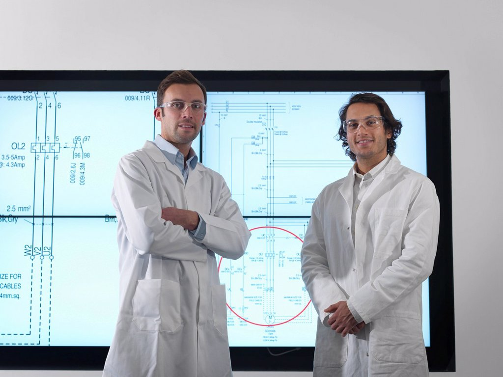 Scientists with diagrams on screen : Stock Photo