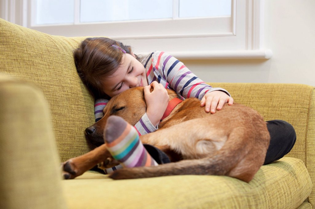 Stock Photo: 1773R-136843 Young girl cuddling her dog on the sofa