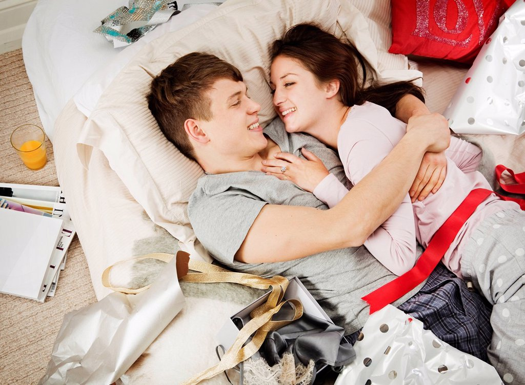 Stock Photo: 1773R-139496 Couple in bed laughing, with presents