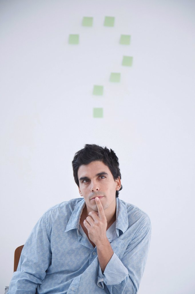Stock Photo: 1773R-139909 Man thinking with post_it note question makr behind him