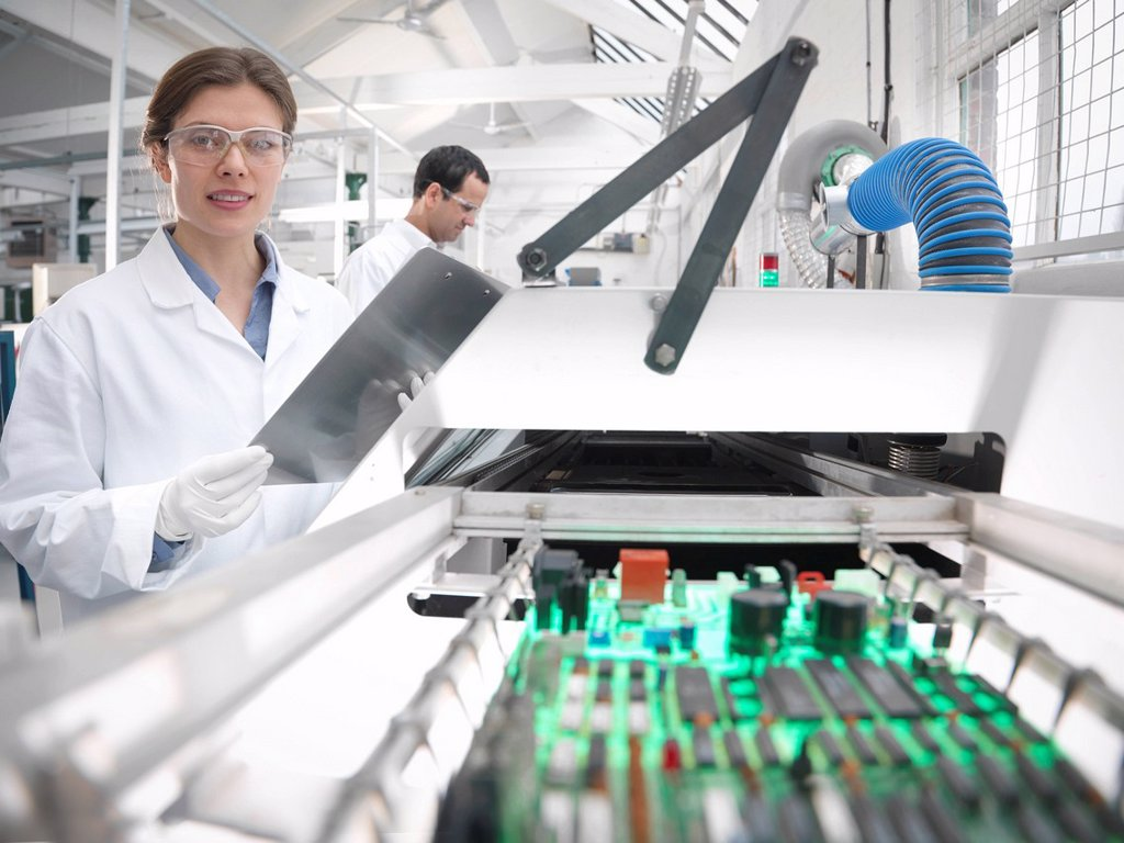 Workers with automated soldering machine : Stock Photo