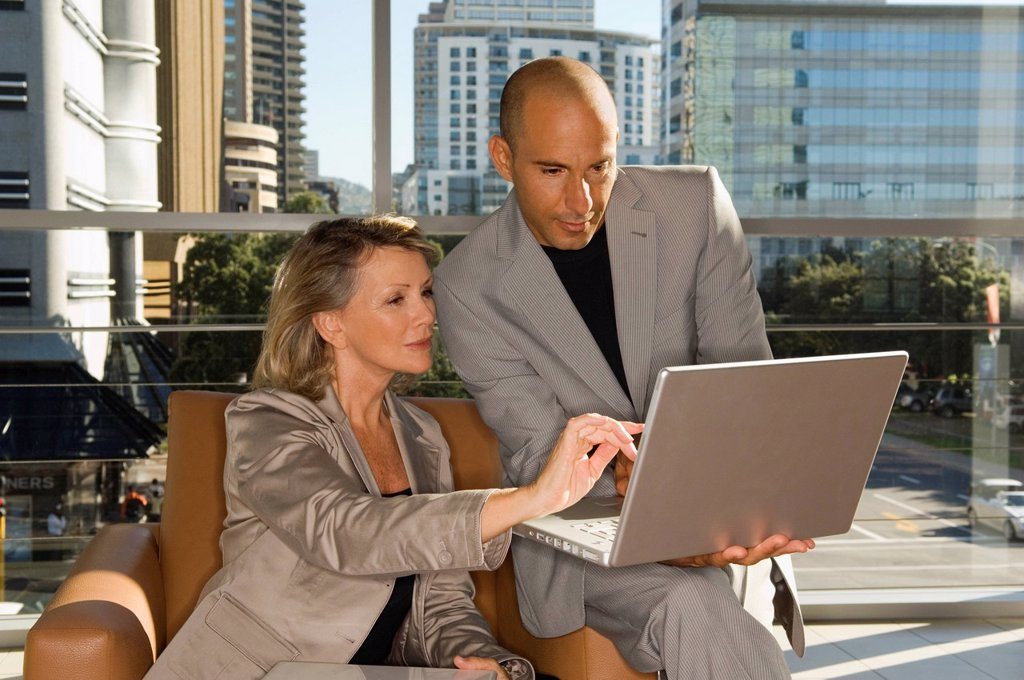 Stock Photo: 1773R-140127 Businessman and woman looking at laptop