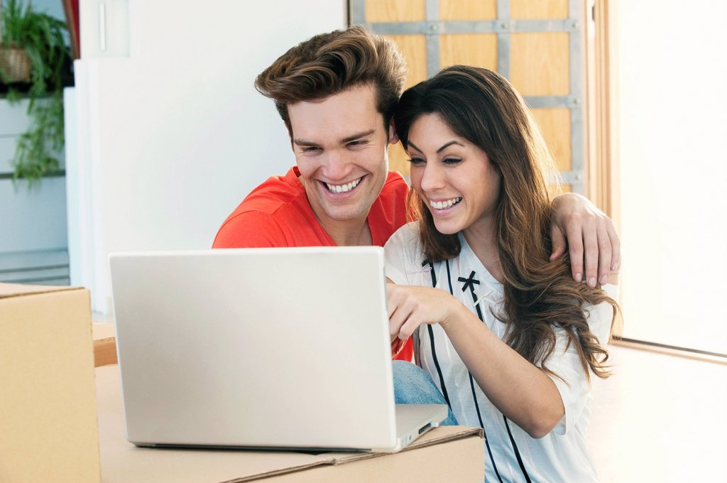 Smiling couple using laptop together : Stock Photo