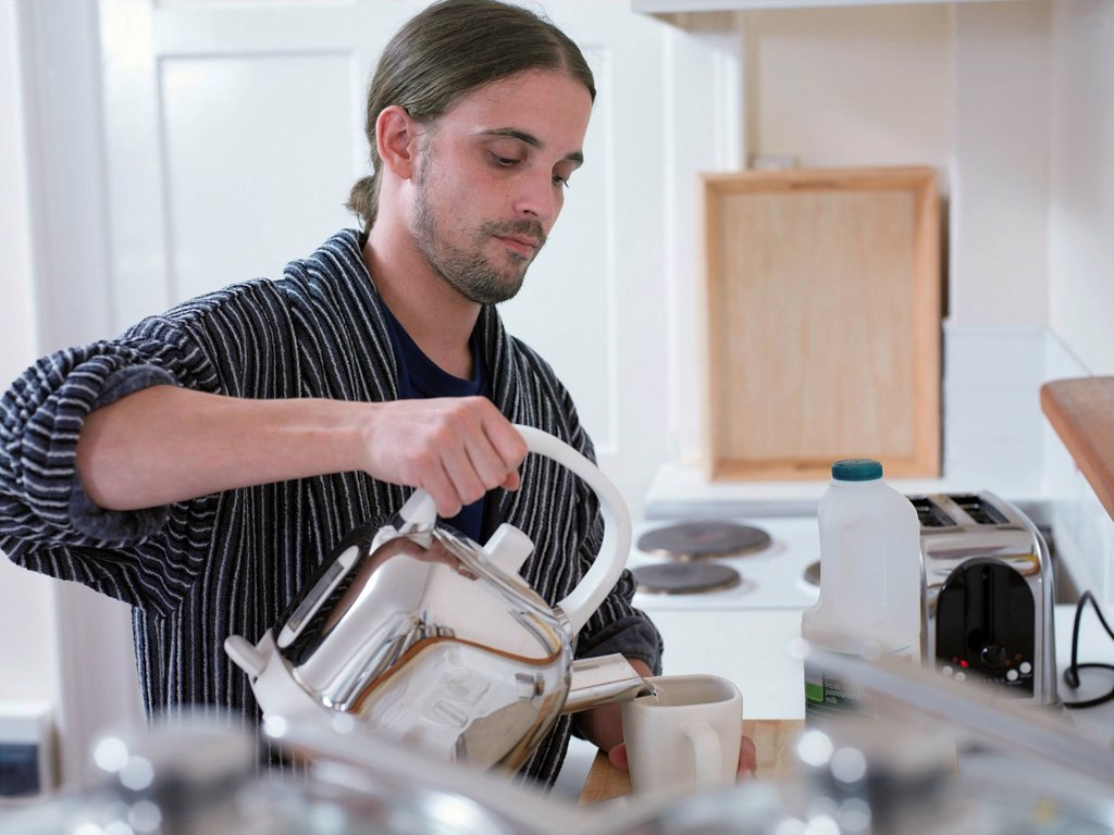 Man making cup of tea in kitchen : Stock Photo