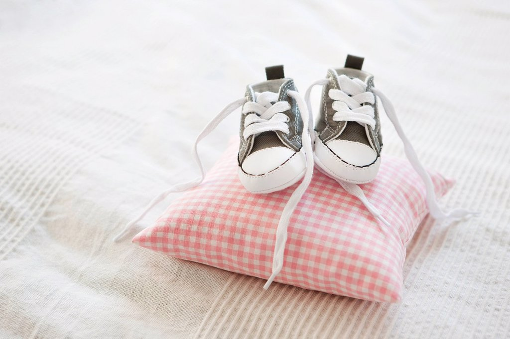 Stock Photo: 1773R-144991 Baby shoes on pillow
