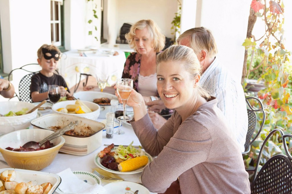 Stock Photo: 1773R-146954 Family eating at table outdoors