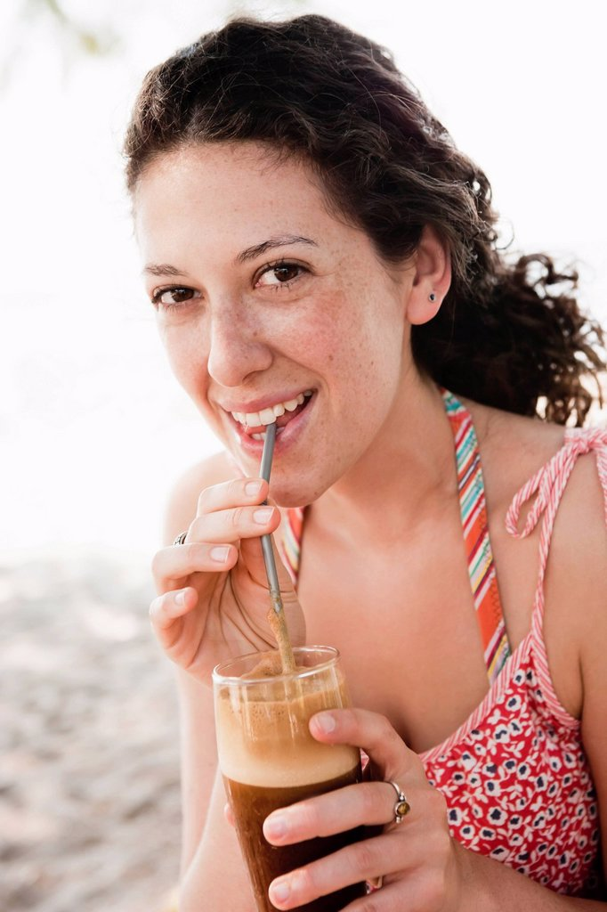 Stock Photo: 1773R-149703 Smiling woman drinking through straw