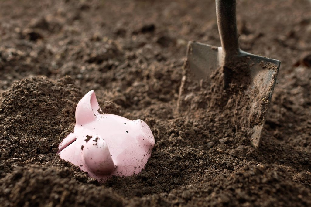 Shovel digging up piggy bank : Stock Photo