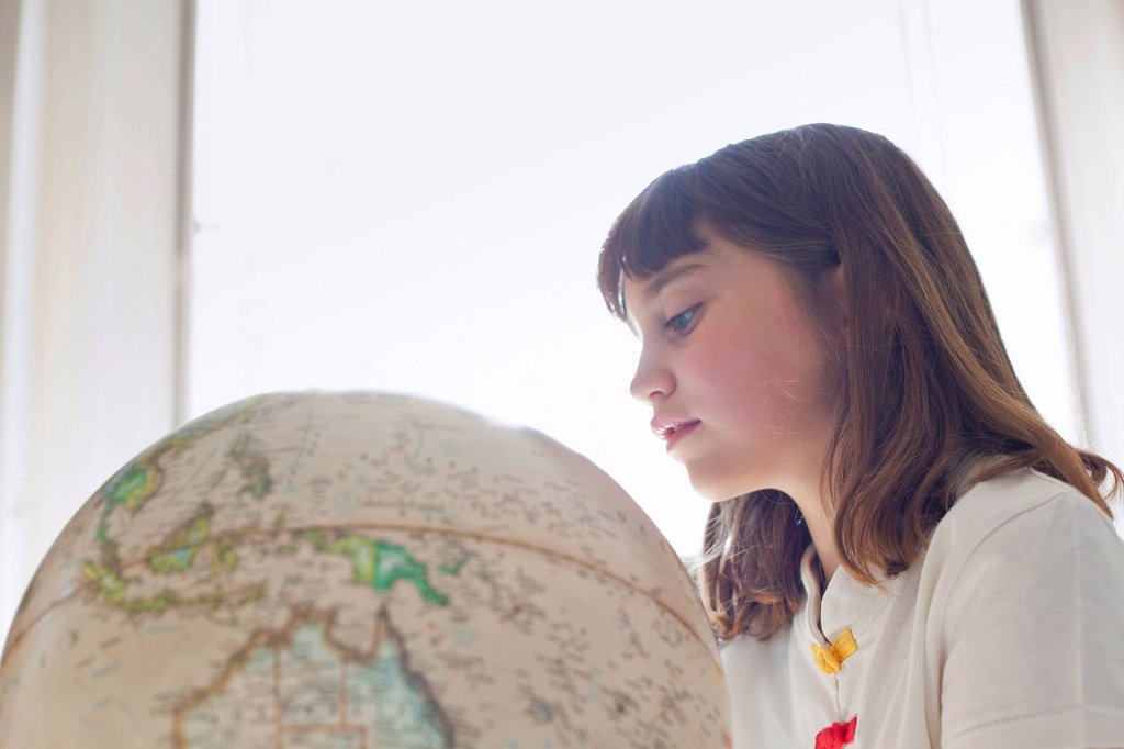 Girl examining globe indoors : Stock Photo