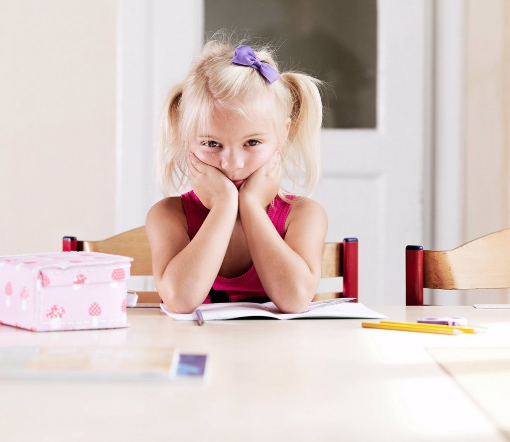 Bored girl doing homework at table : Stock Photo