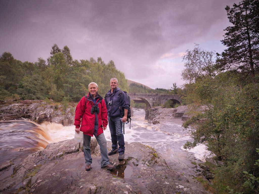 Hikers standing by rocky river : Stock Photo