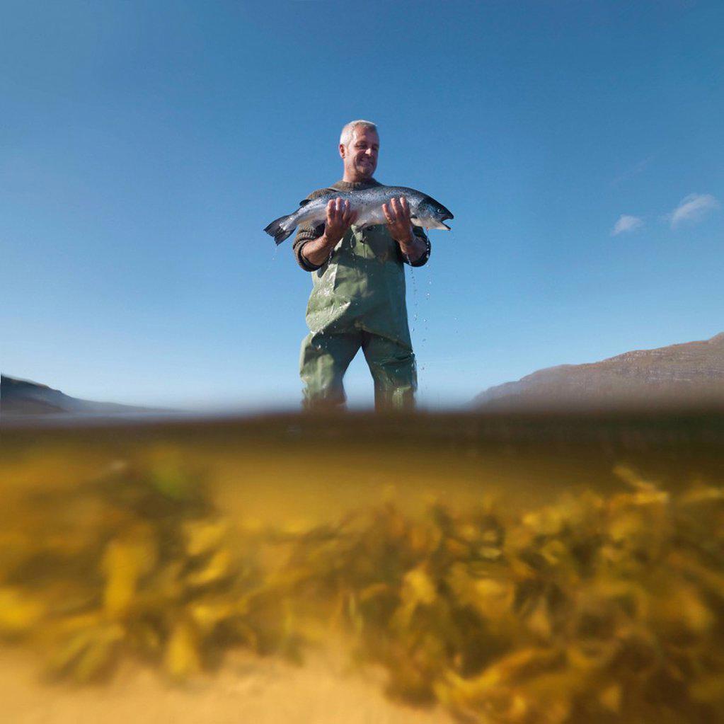 Fisherman with salmon in still lake : Stock Photo