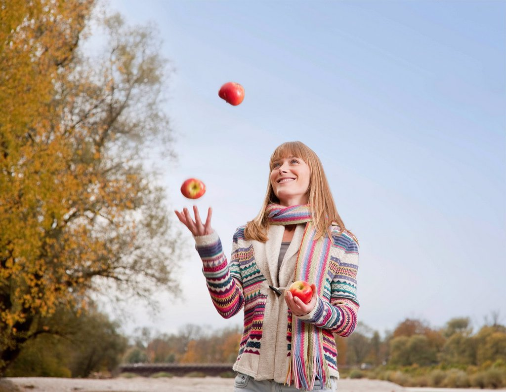 Woman juggling apples outdoors : Stock Photo