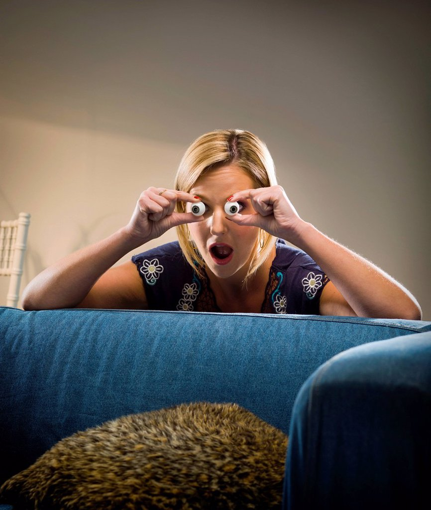Woman holding glass eyes in living room : Stock Photo