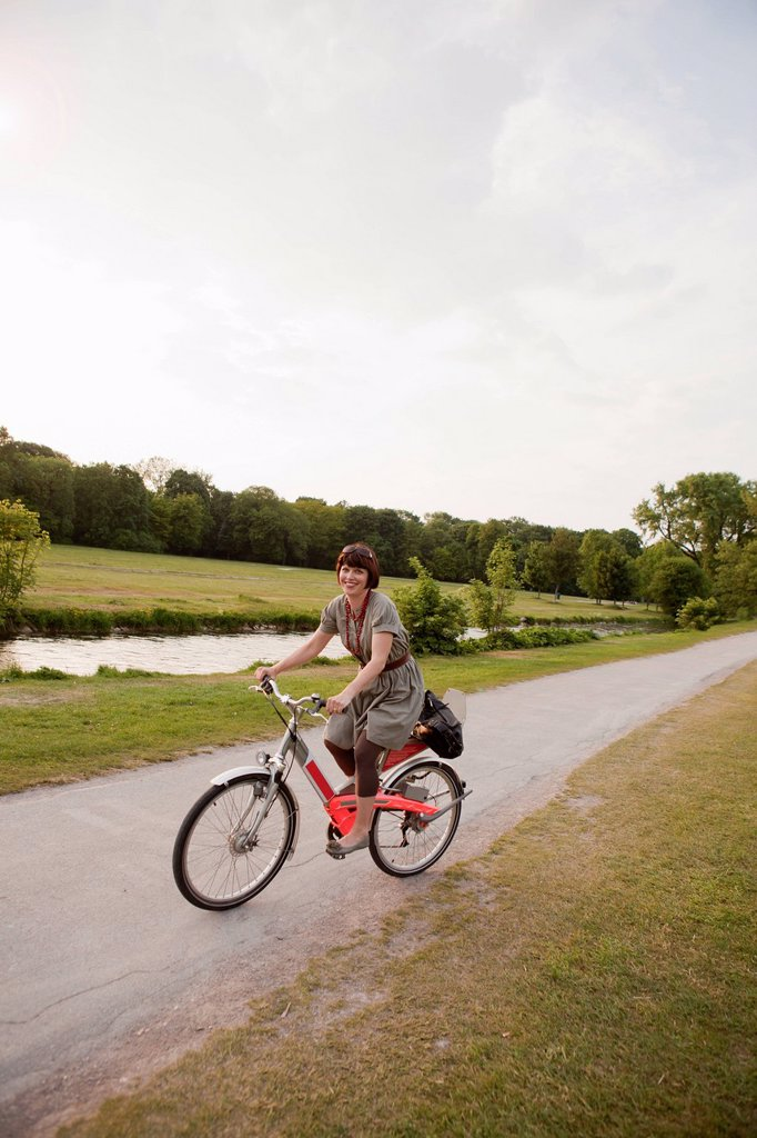 Woman riding bicycle on rural road : Stock Photo