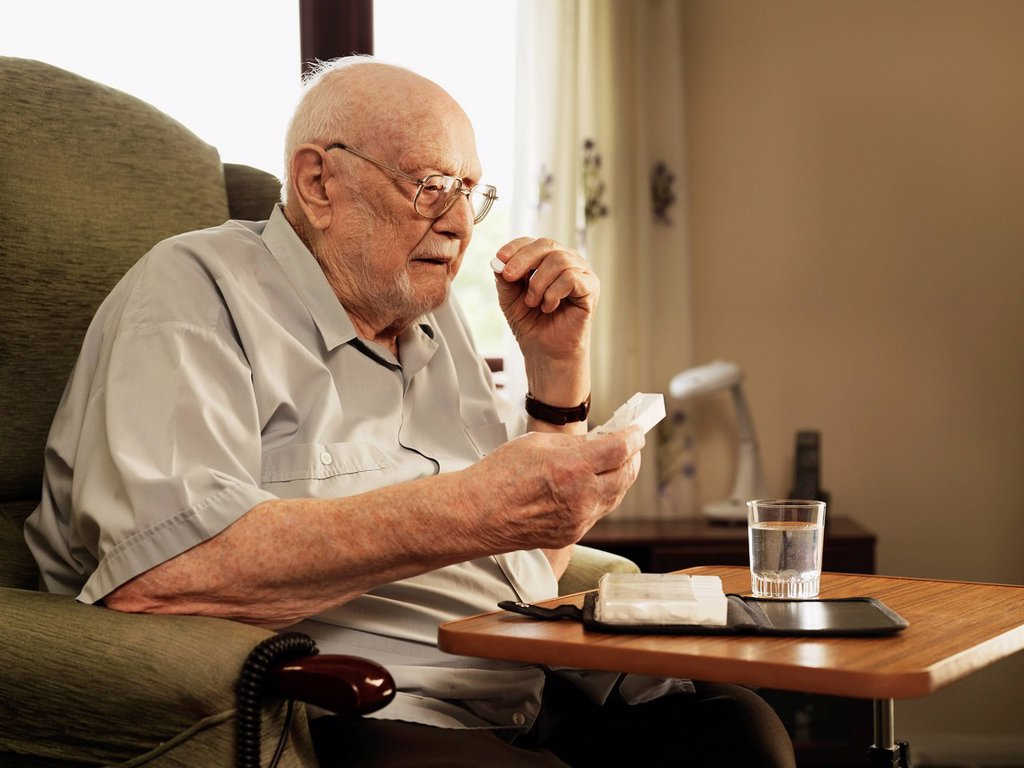 Older man taking medication in armchair : Stock Photo