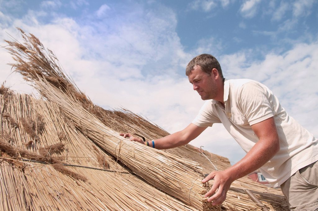 Stock Photo: 1773R-168645 Man working on straw roof