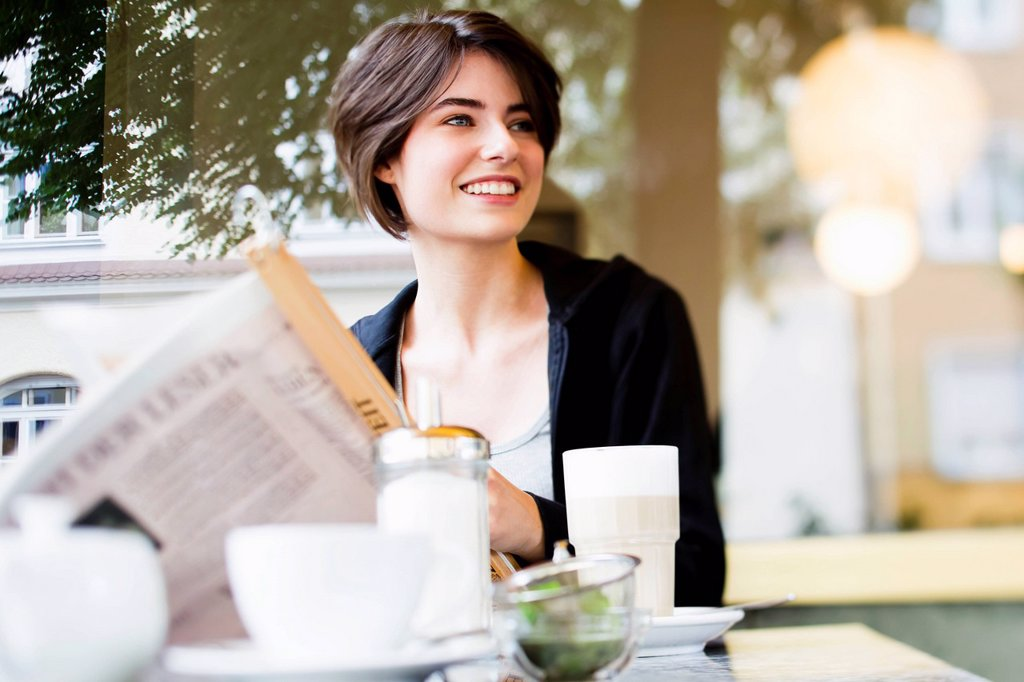 Stock Photo: 1773R-168891 Woman reading newspaper in cafe