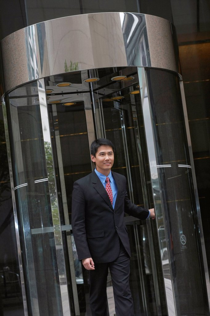 Stock Photo: 1773R-169815 Businessman exiting revolving door