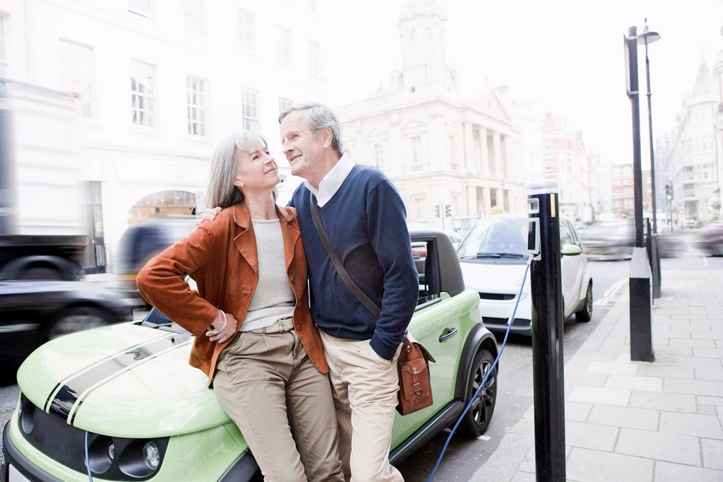 Stock Photo: 1773R-170564 Couple charging electric car on street